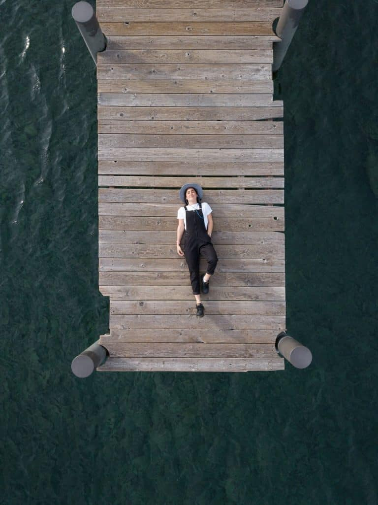 woman in black overall lying down on wooden dock