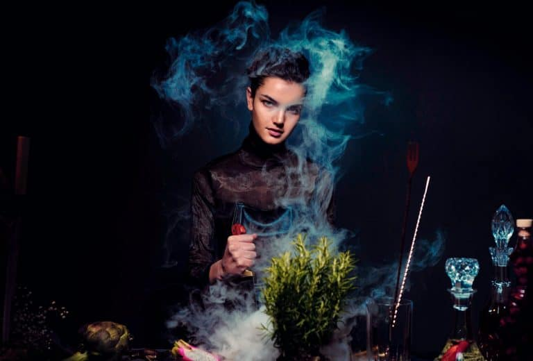 alluring young woman preparing potion against black background