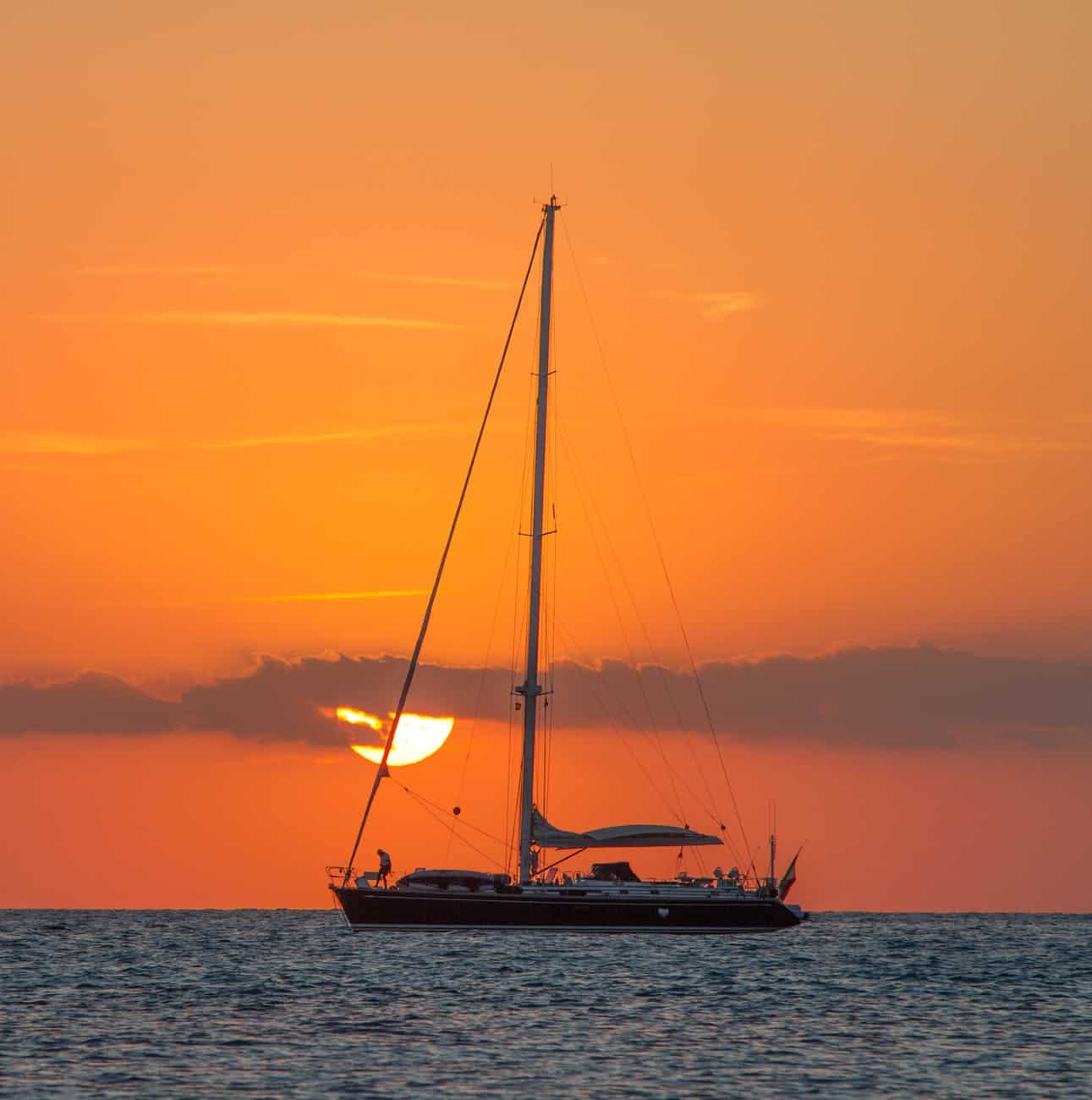 sailboat on body of water during sunset