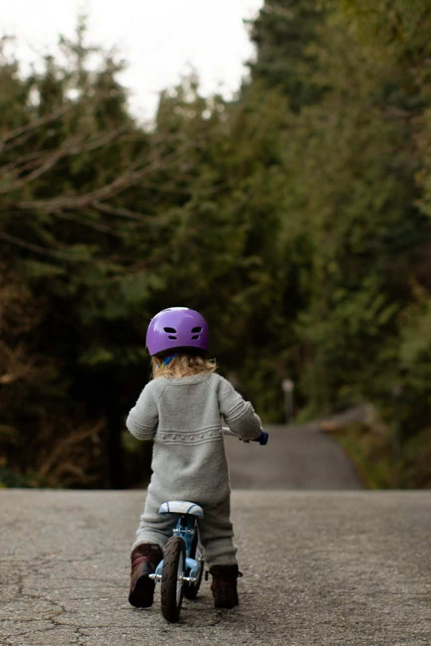 anonymous kid in helmet riding run bike on pavement in countryside