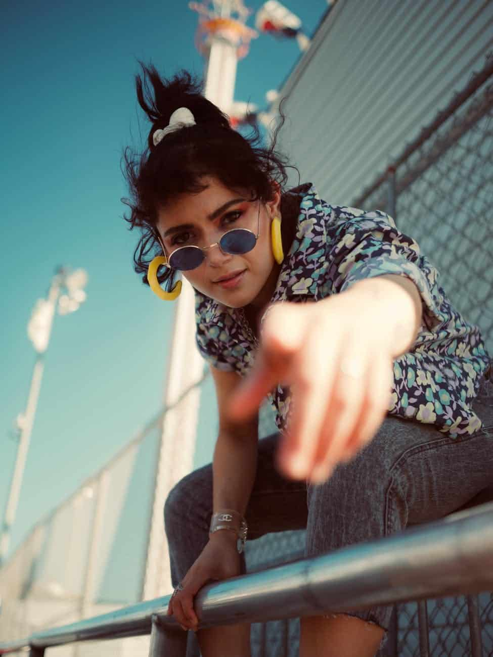 selective focus photo of woman in floral shirt grey jeans and sunglasses pointing finger