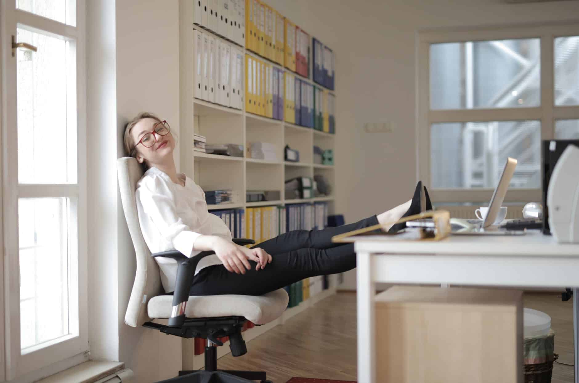 relaxed female secretary with feet on table in workplace
