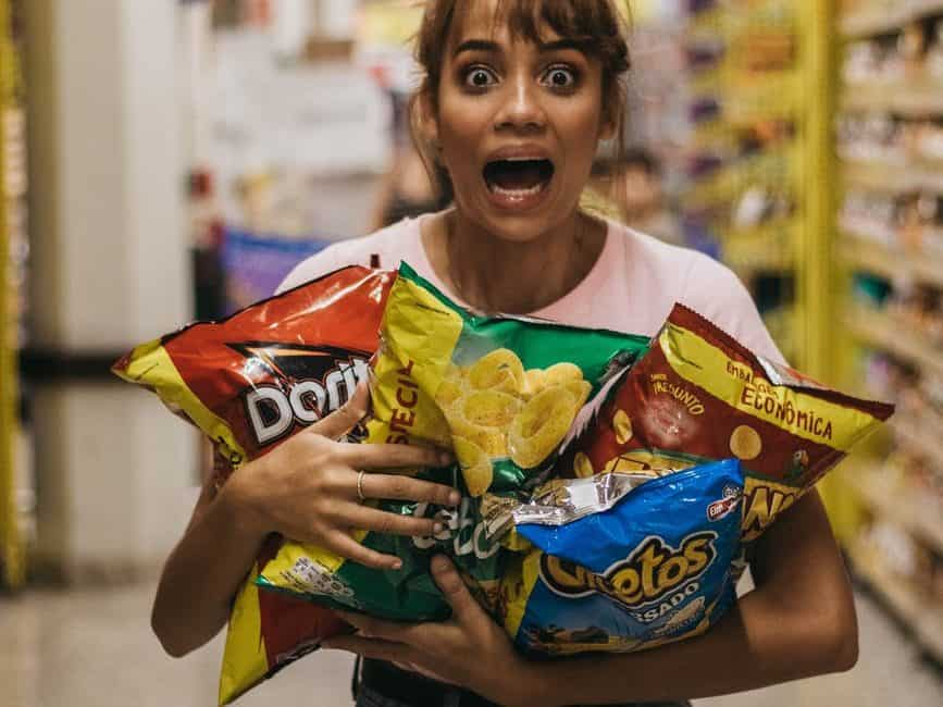 expressive woman holding packs of assorted chips in market and shouting
