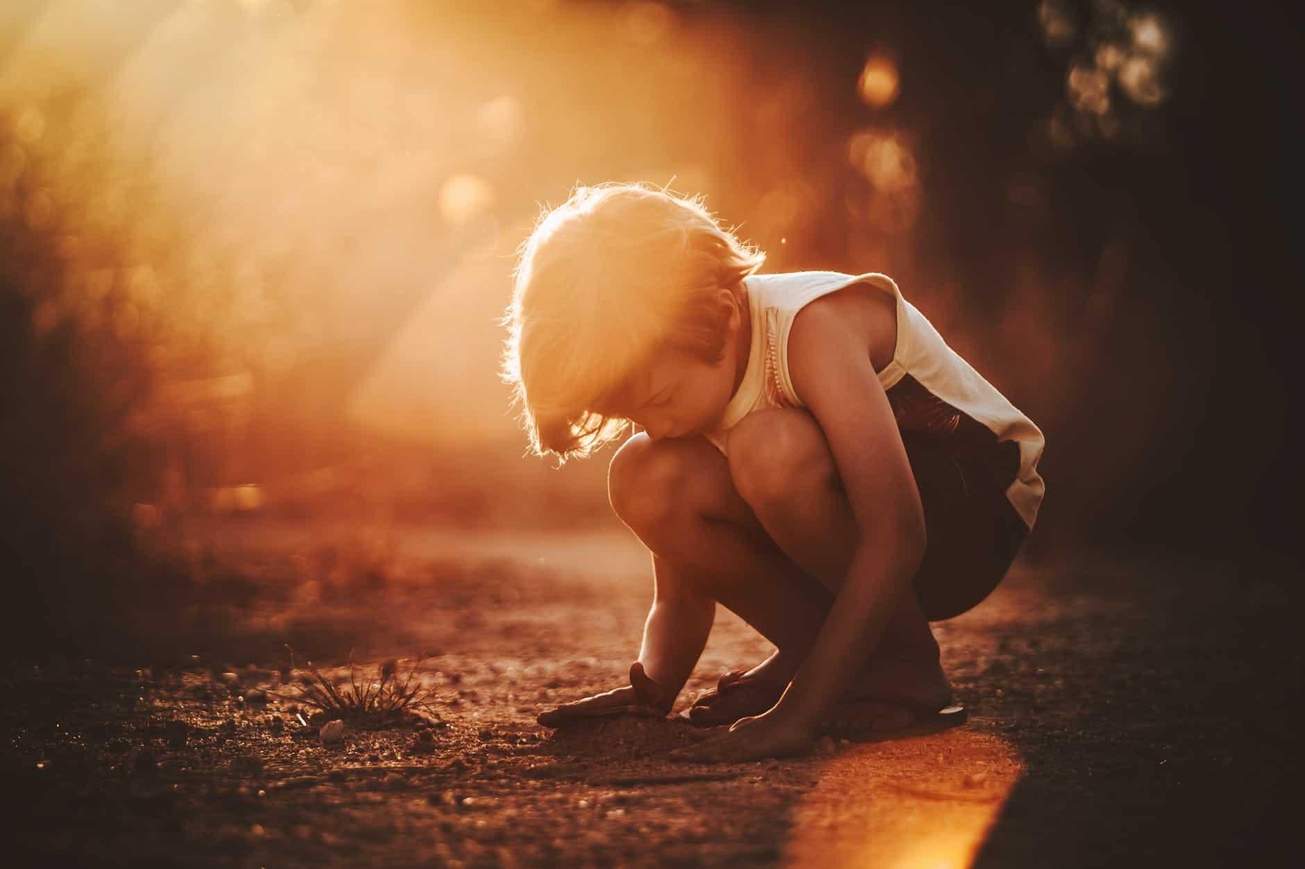 little boy squatting on sandy ground