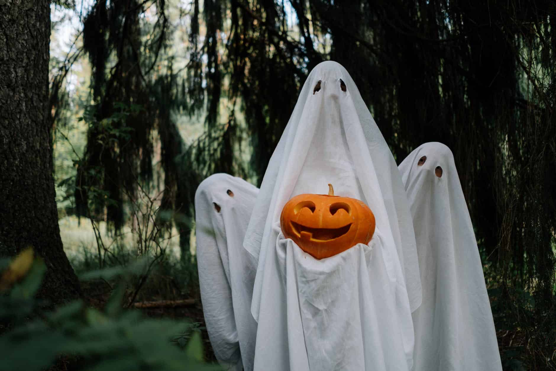 ghosts holding a carved pumpkin