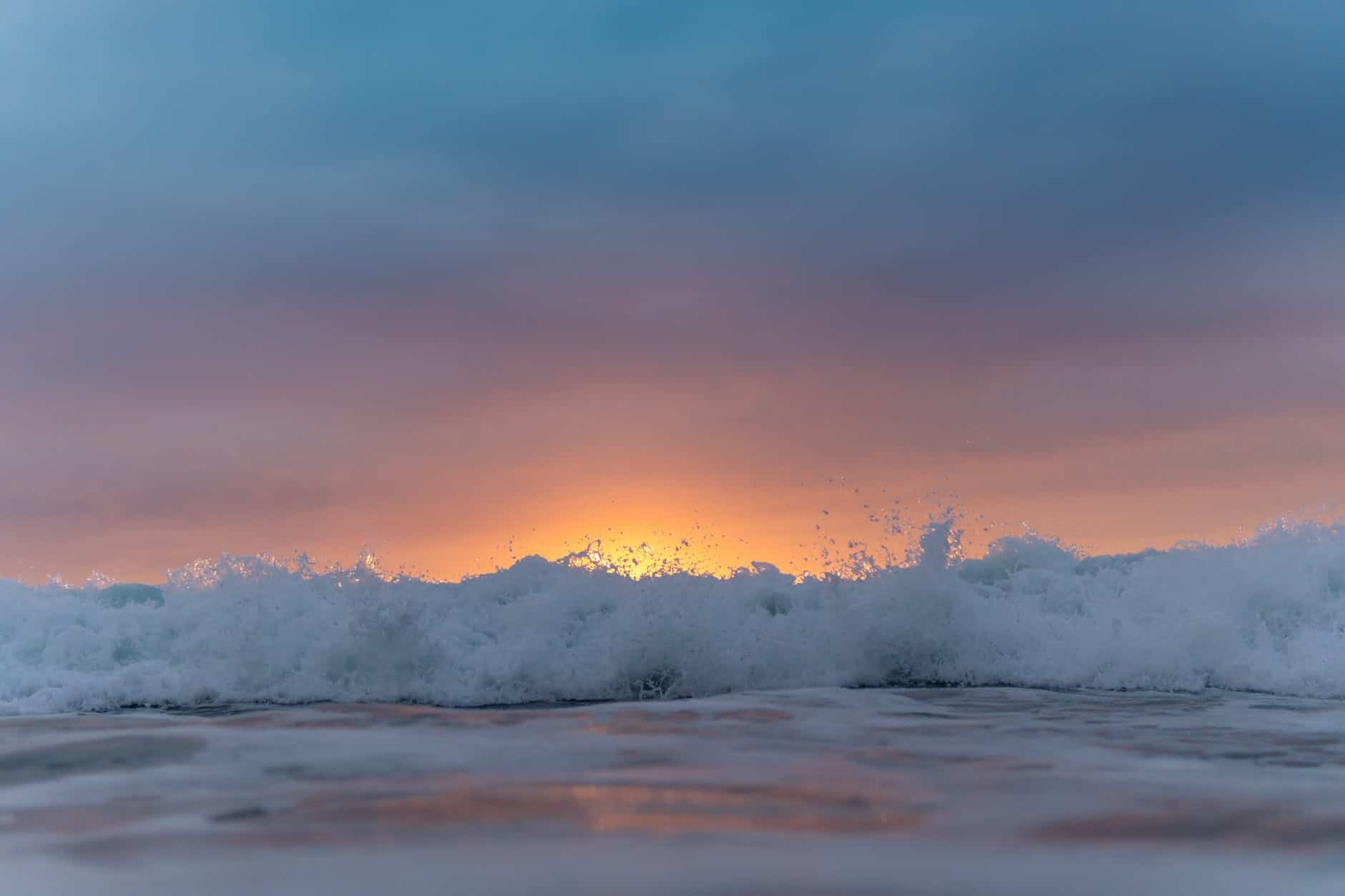 sunset sky over waving sea washing shore