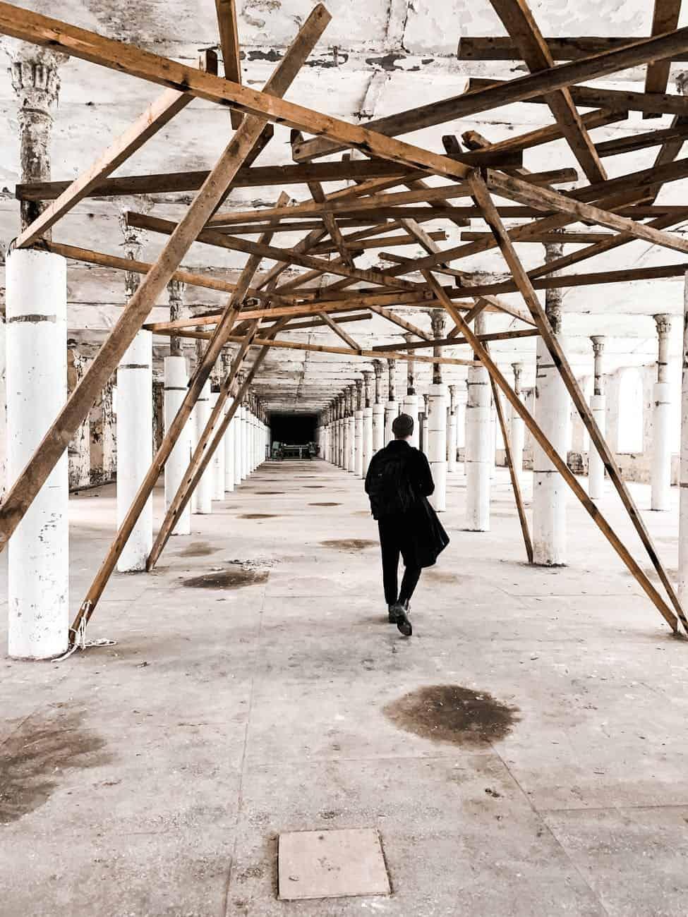 unrecognizable man walking in building corridor under reconstruction