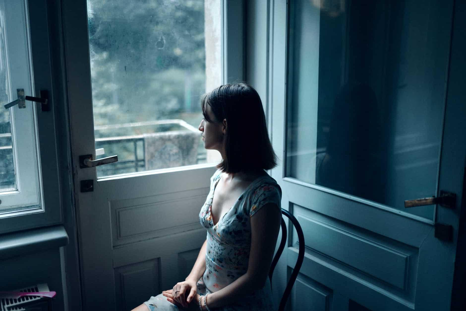 woman sitting near white wooden door