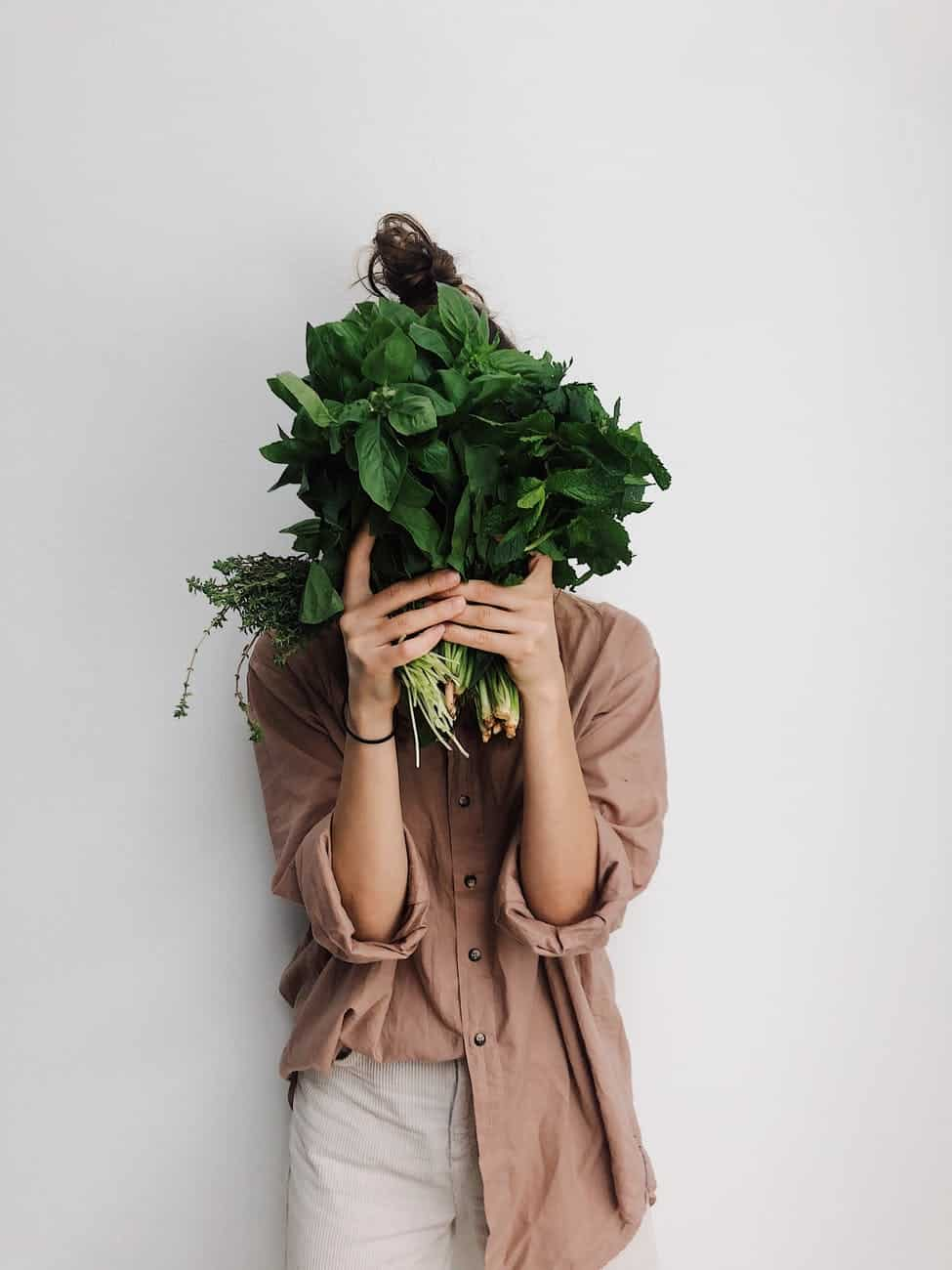 person holding green vegetables representing handing from real change