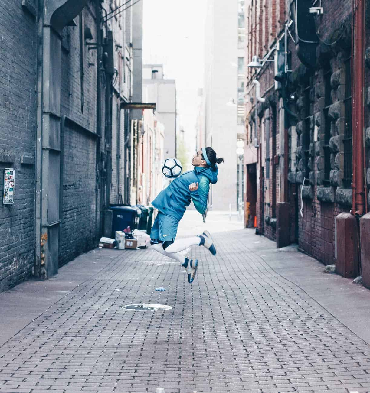 male football player jumping with ball in city