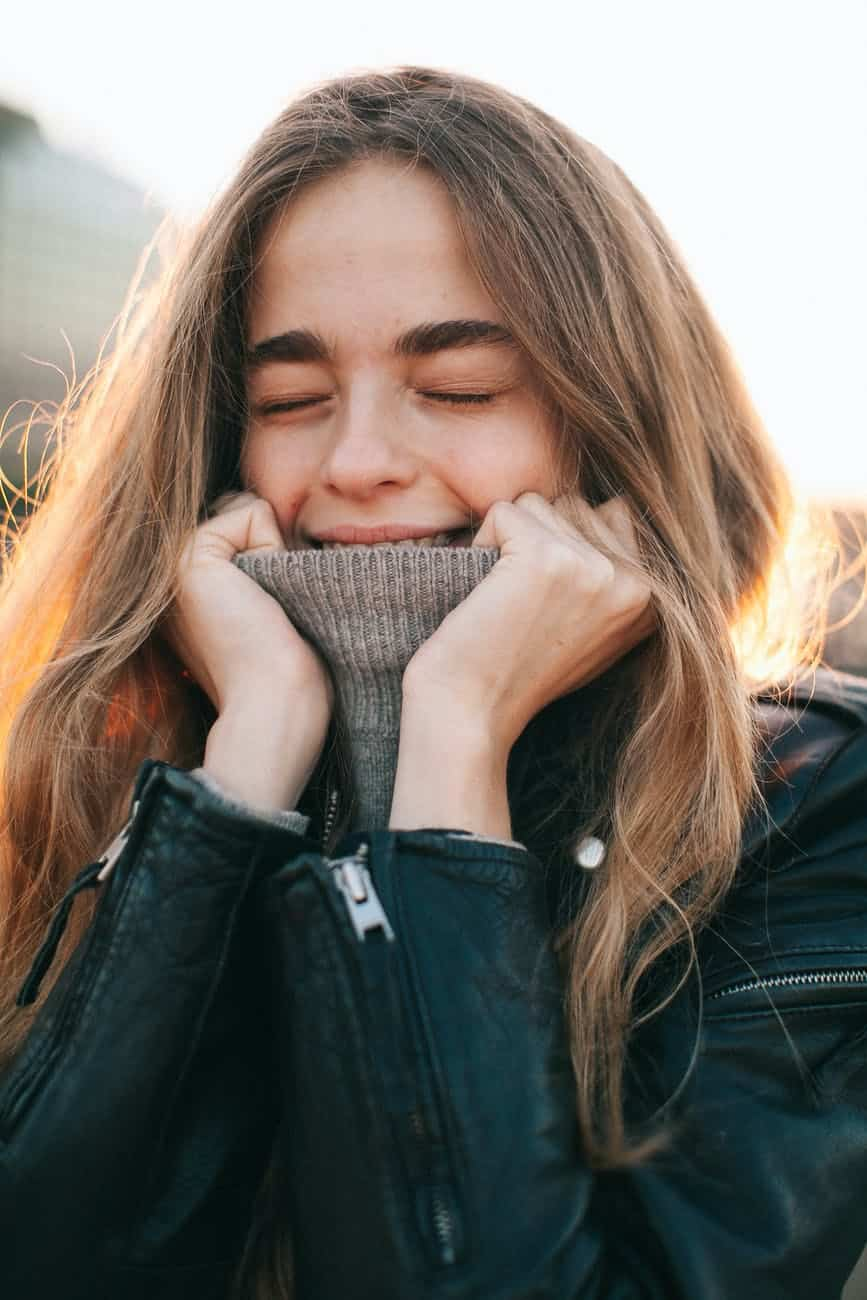 cheerful young woman with eyes closed covering mouth with turtleneck on street