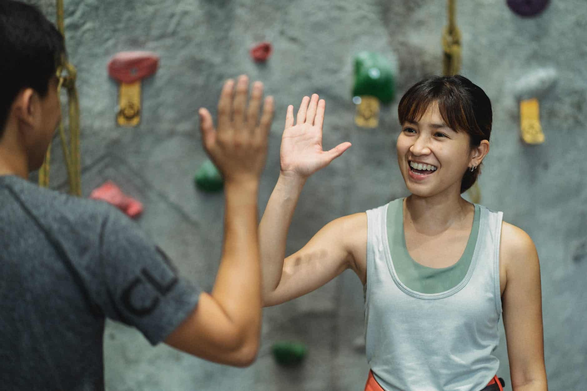 happy ethnic female climber with anonymous male friend giving high five in gym