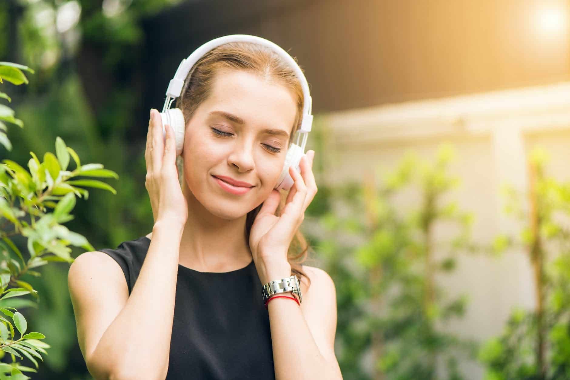 woman wearing black sleeveless dress holding white headphone at daytime Listening to find truth in the silence
