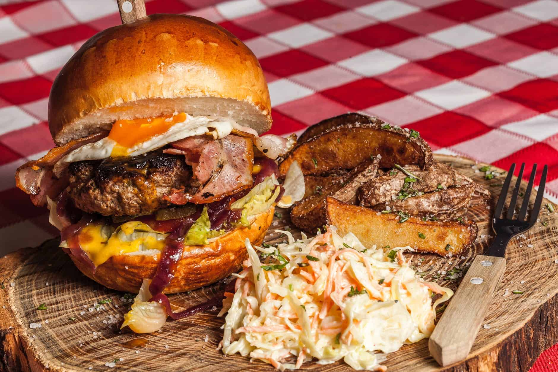 meat burger with coleslaw on side and brown handled fork