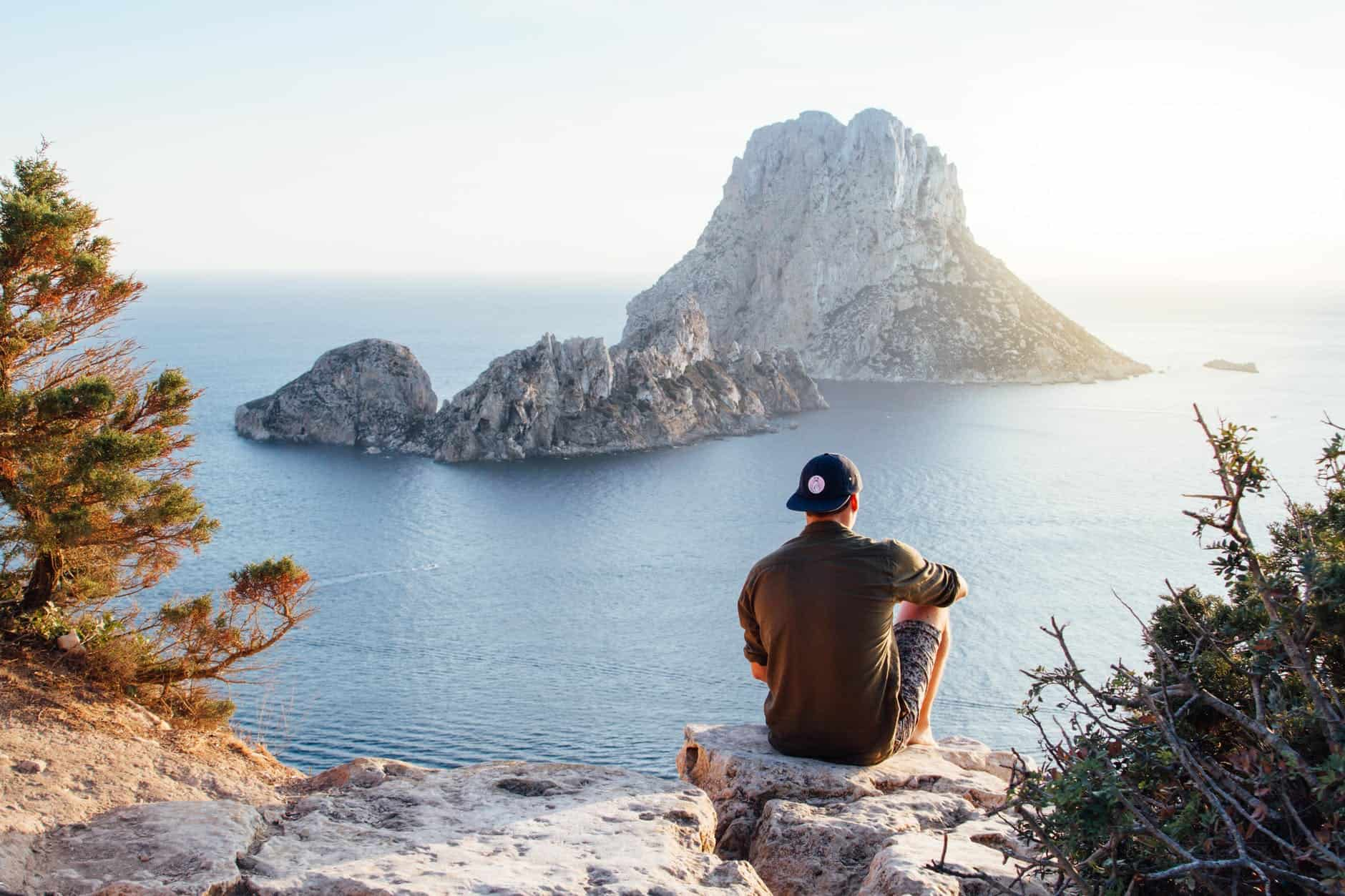 rear view of man sitting on rock by sea Listening to find truth in the silence