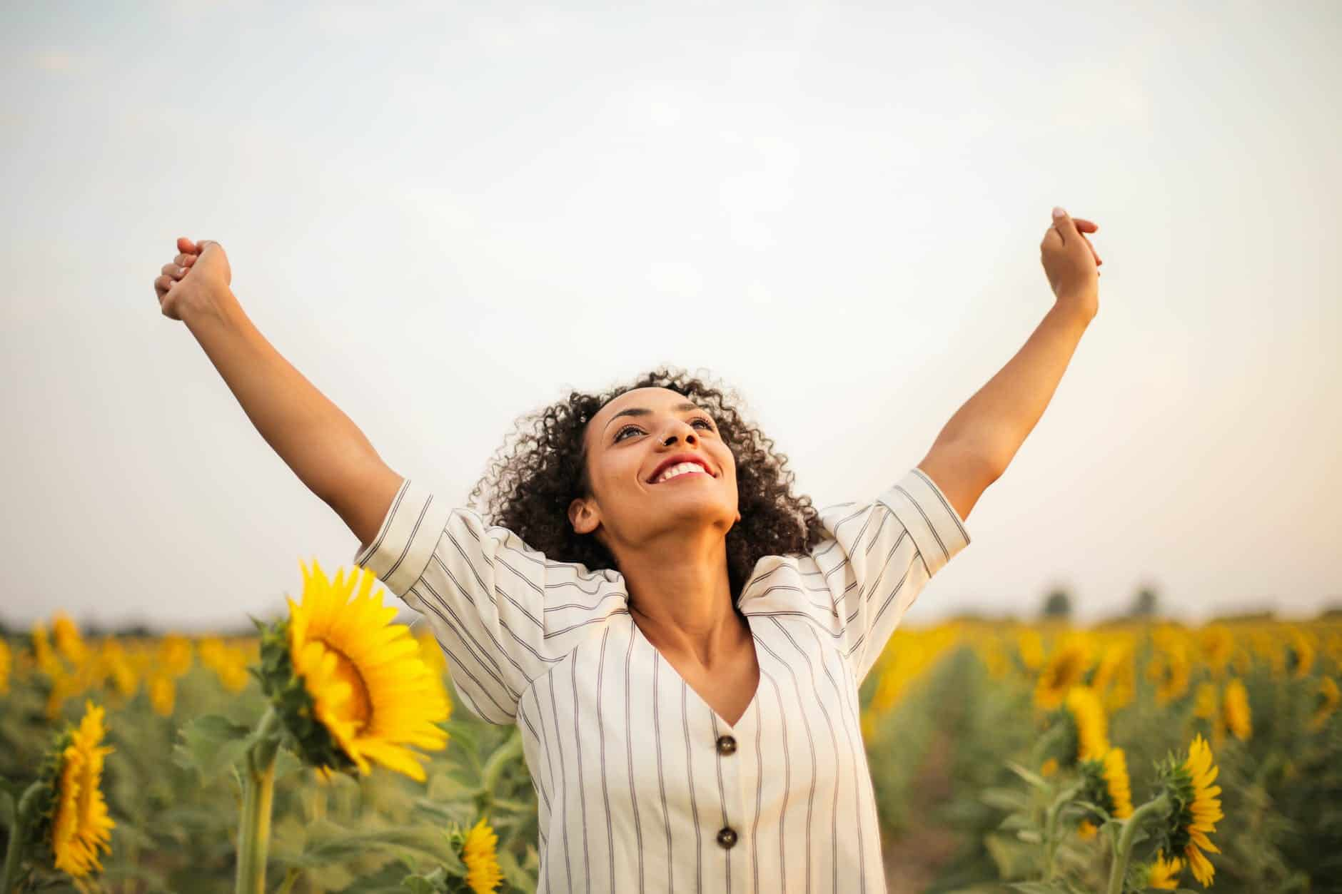 photo of woman standing on sunflower field