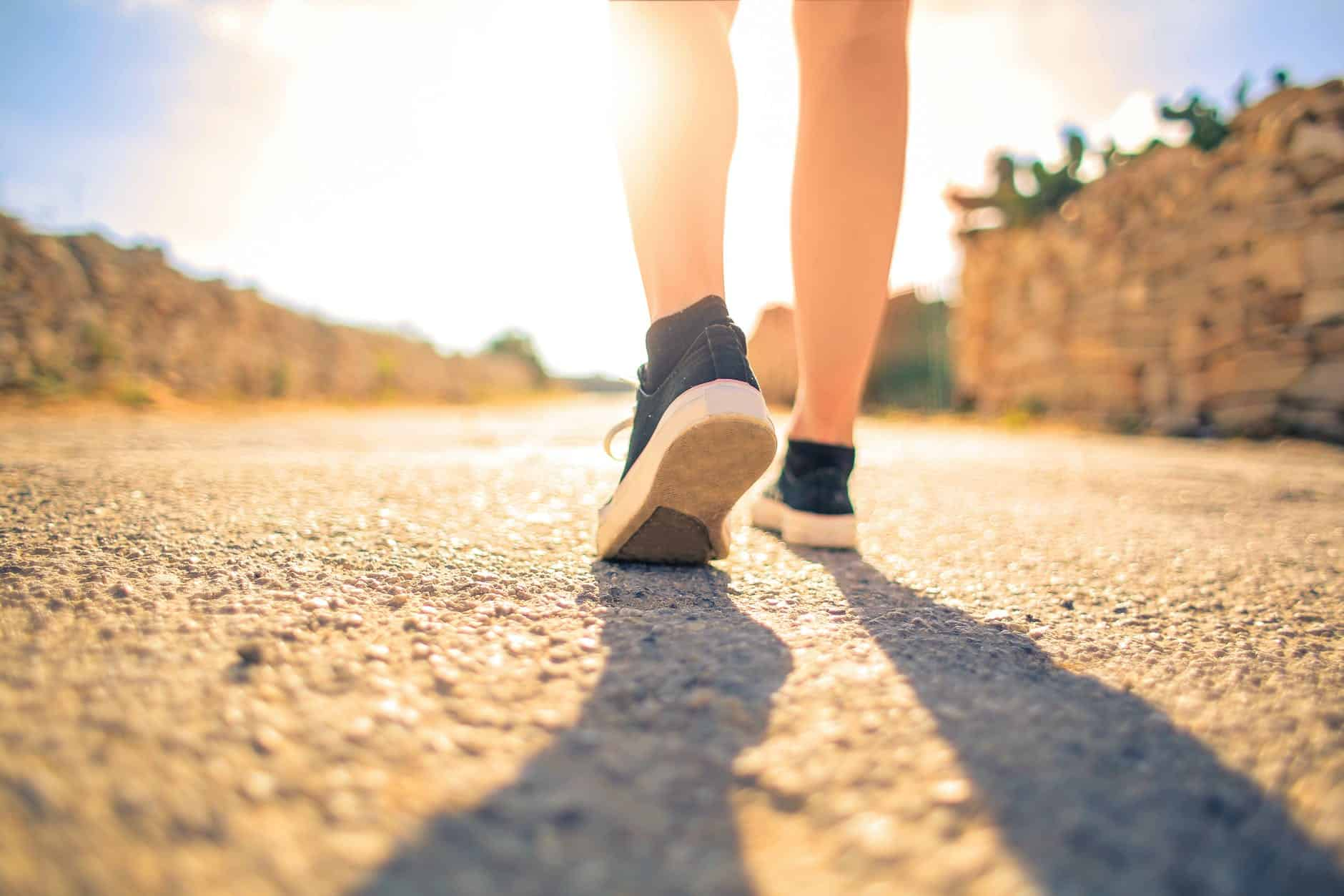 woman walking on pathway under the sun Mastering Your Mind