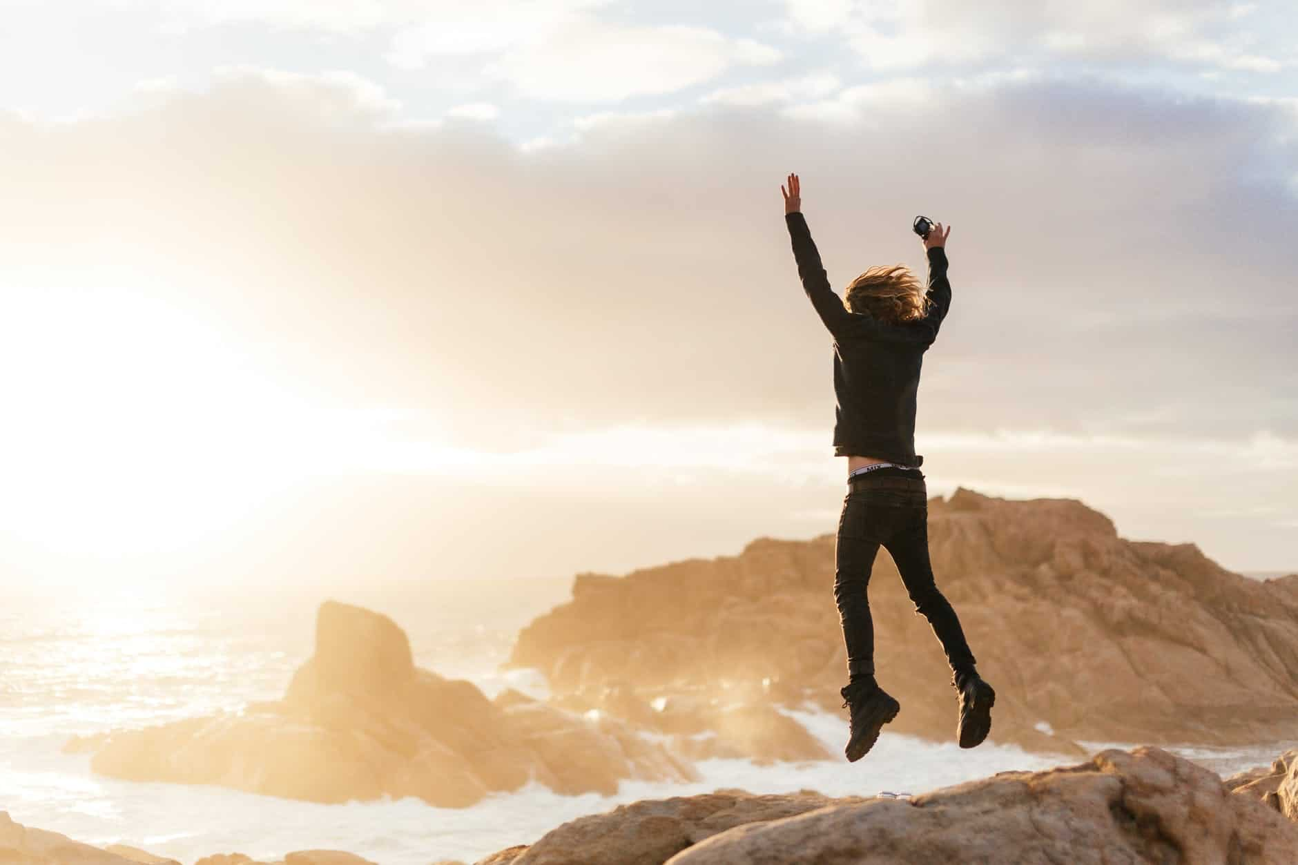 unrecognizable man jumping on stones near sea The Key to Effective Leadership
