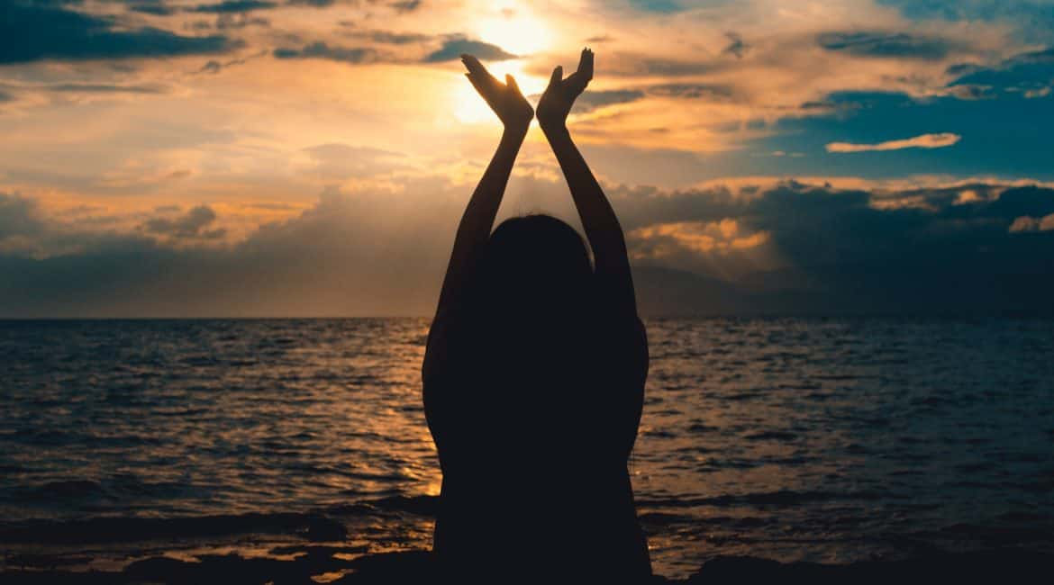 person raising hands near sea at sunset