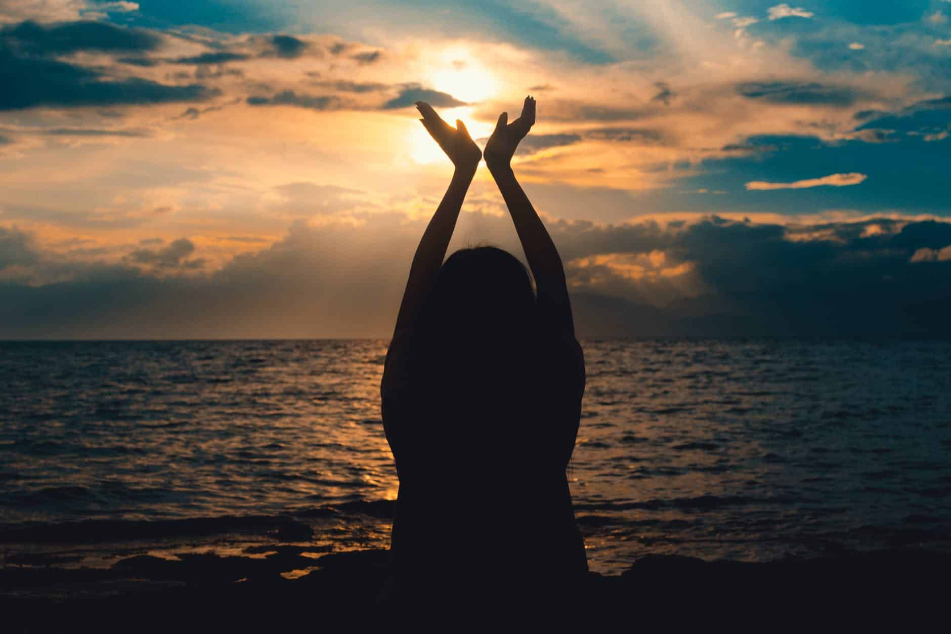 person raising hands near sea at sunset Letting Go
