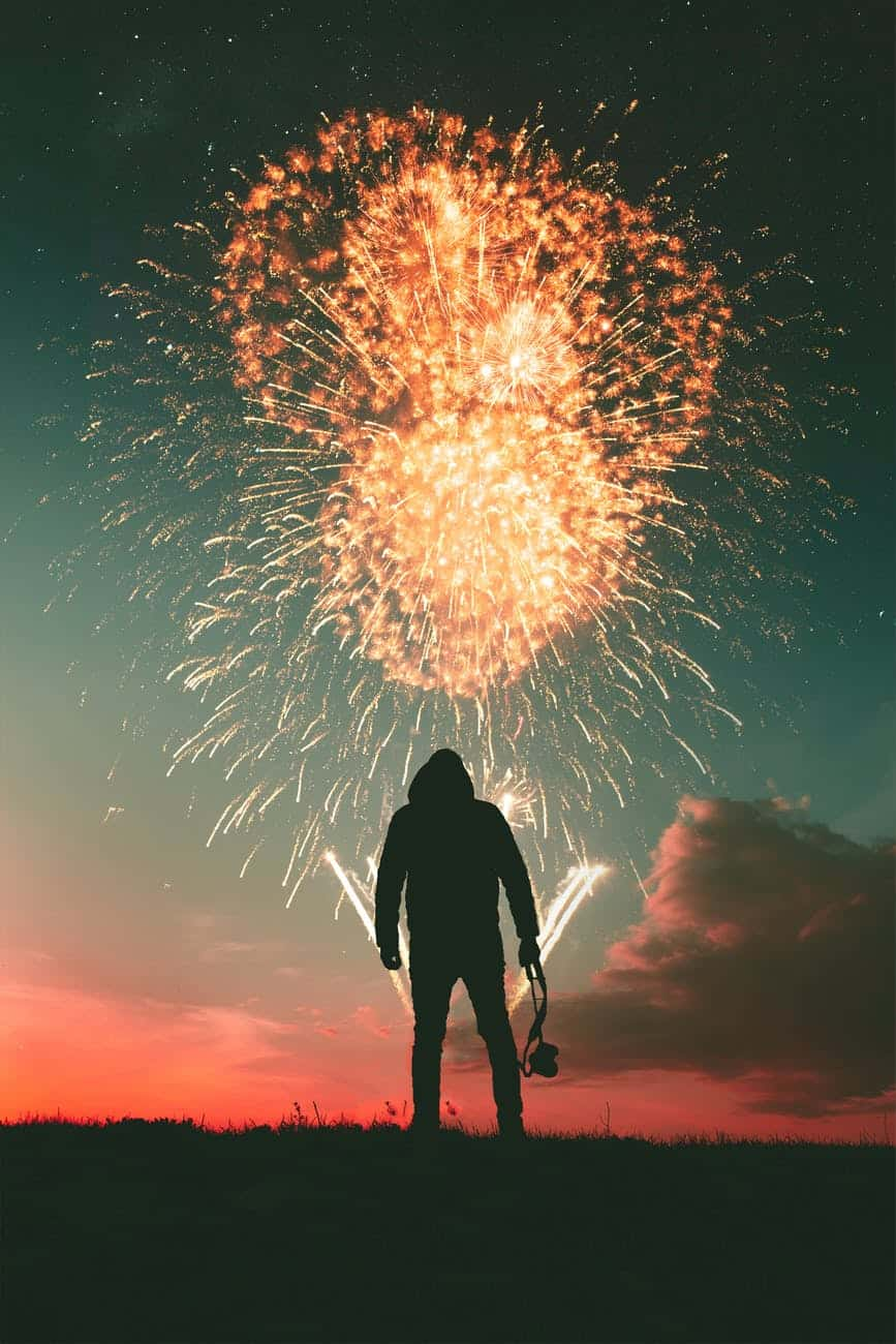 silhouette photo of standing man holding camera looking at fireworks display Letting Go
