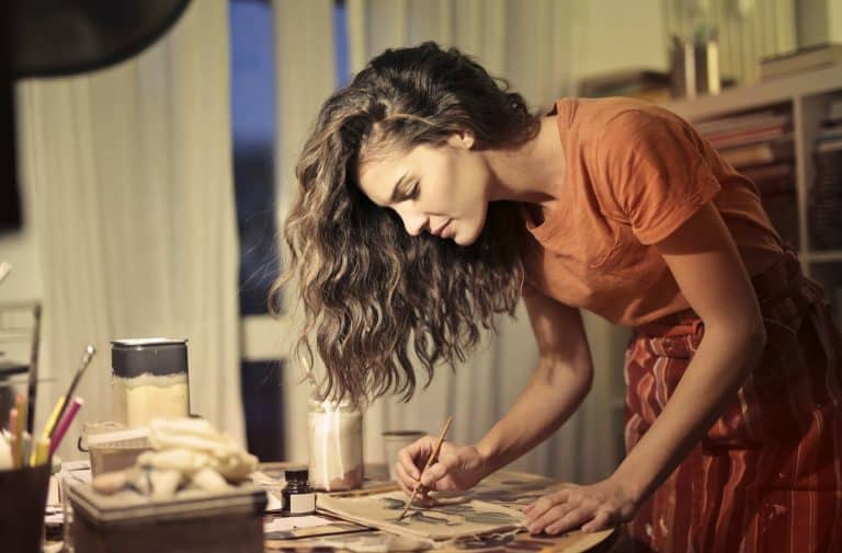 creative female artisan drawing in workshop