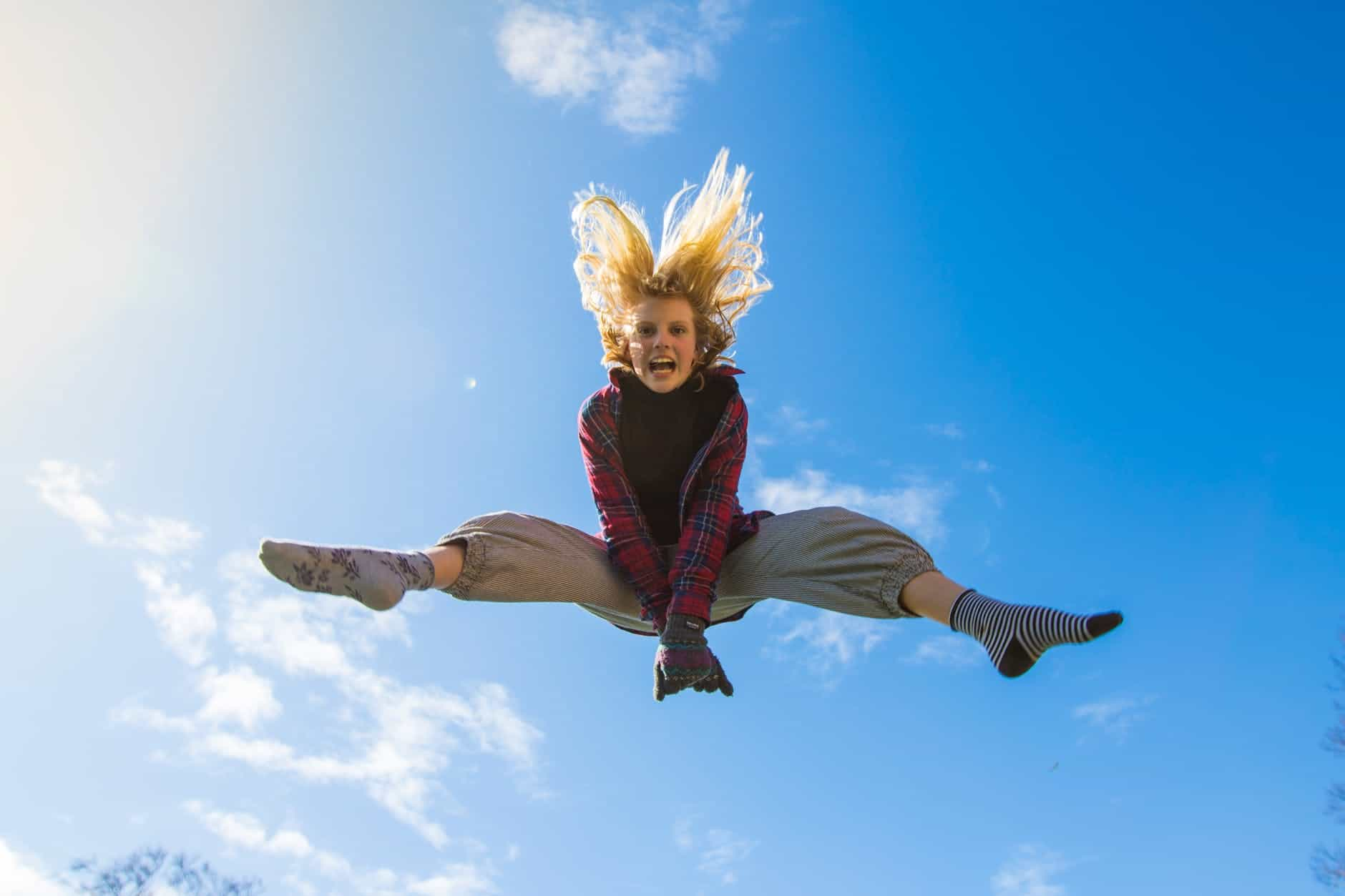 woman jumping under blue sky Power of Meditation