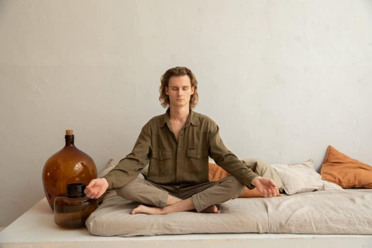 serene man meditating in lotus pose on sofa