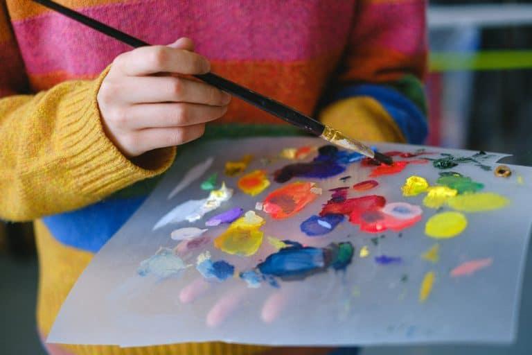 unrecognizable painter mixing colors on paper