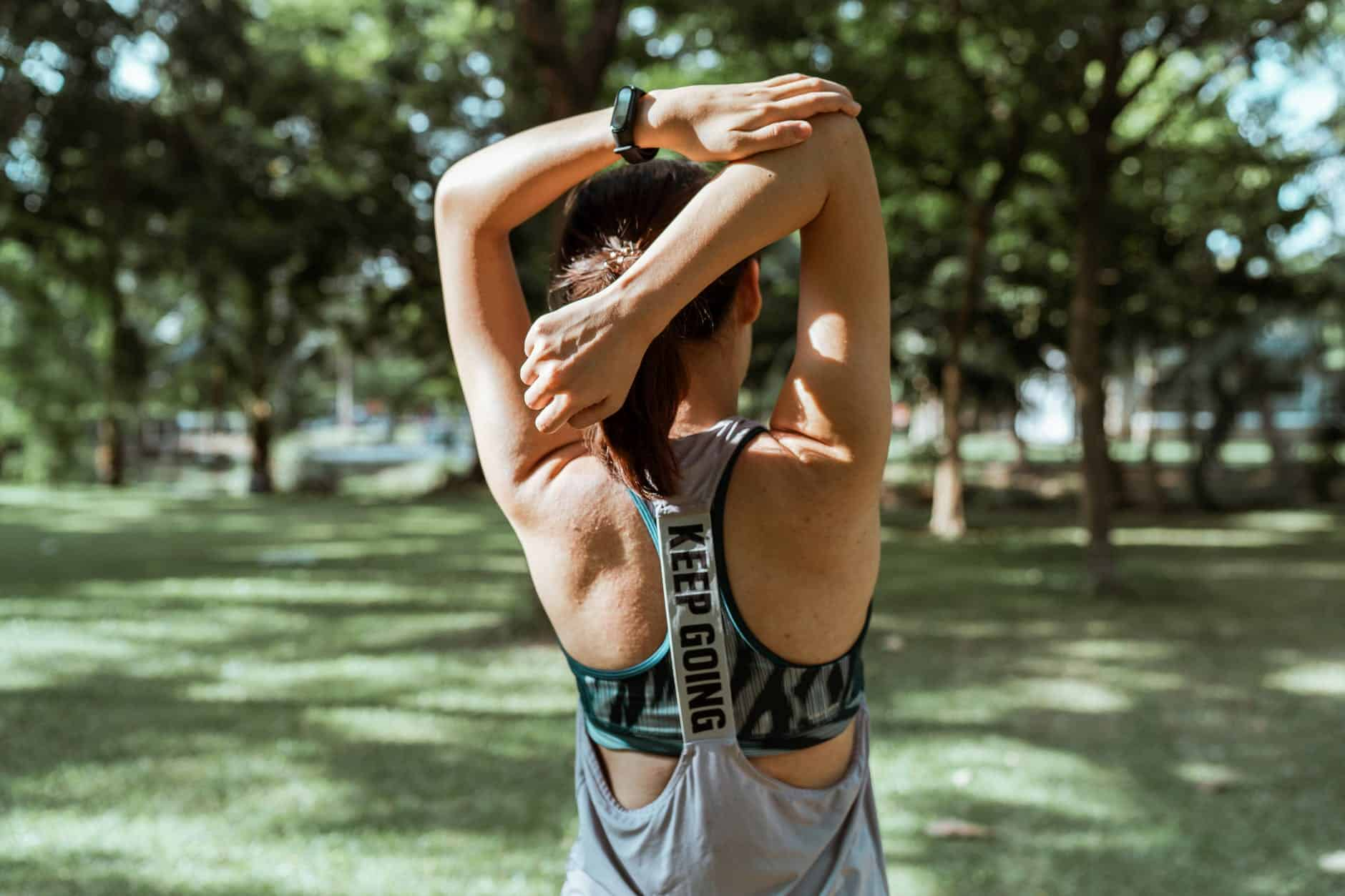 unrecognizable female athlete stretching muscles of arms and back - make change happen